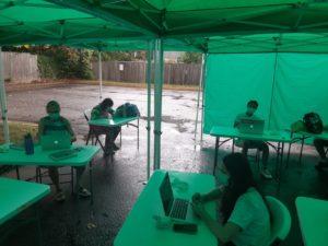 high school class in outdoor classroom tents during rain